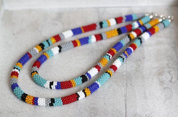 Bijou dinspiration africaine collier inspiré de Double-brin, collier deux niveaux, rayures colorées collier, collier corde Style zoulou, Maasai perlage ***  One-of-a-kind, deux brins, à deux vitesses, collier coloré, inspiré par les bijoux en perles africaine, en technique de crochet perle. Matériaux: Perles japonaises dans les tons de jaune, couleurs bleu cobalt, turquoises, gris, noirs, rouges et blancs, ainsi que des composantes en métal couleur argent.  Il se compose de deux volets…