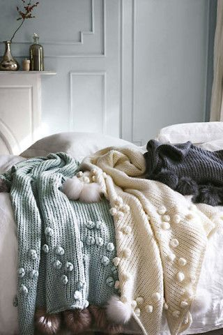 The loose knit and fuzzy poms of this fireside-worthy throw are oh-so-soft to the touch.