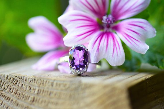 This ring features a bright, rich purple, 5 carat oval cut natural Brazilian amethyst, that flashes bits of pink in the light. The accompanying stones are tiny sparkling micro-pave cubic zirconia that hug the top and bottom of the amethyst and meet the bare shining silver band. Very comfortable to wear and absolutely stunning in natural light.  Jewellery Specifications:  Metal: .925 marked solid sterling silver. Finish: Rhodium plated. Gemstone: 5ct natural Brazilian amethyst Stone…