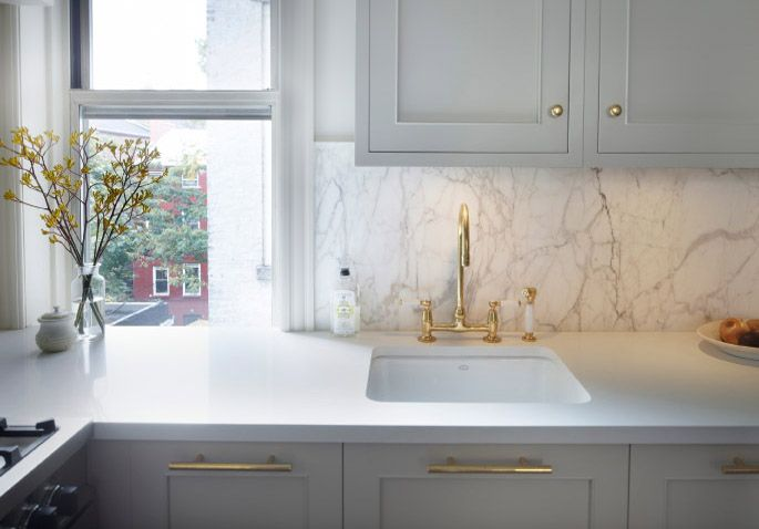Pale grey cabinetry, brass hardware, marble splashback and engineered-stone bench tops.