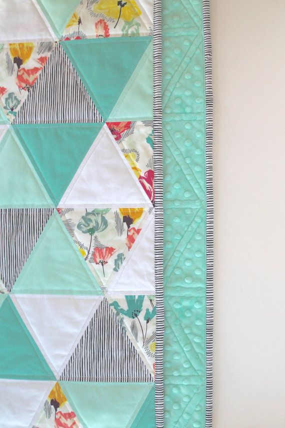 The colors in this quilt make me think of running through a field filled with wildflowers in the summertime. The triangle pattern in addition to the color combo is perfection. Your little one will just love this quilt and it is sized to be used throughout childhood.  This quilt has been machine-pieced and is made of high-quality 100% cotton prints in mint, turquoise, yellow, pink, and white backed in a mint minky dot fabric with a layer of cotton batting in between. The three layers are…