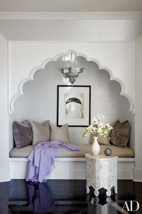 Moroccan style bedroom reading nook is filled with a bench lined with lilac and gray velvet pillows illuminated by a Moroccan lantern alongside a bone inlay Moroccan accent table atop a glossy black floor.