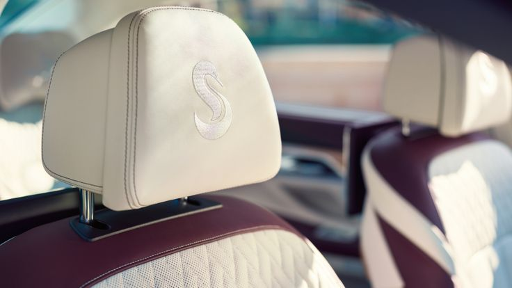 The yacht maker's swan logo is embroidered on the front headrests and plush leather pillows on the rear seats.