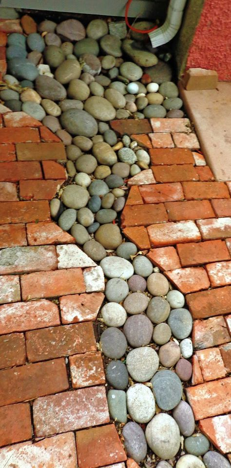 attractive downspout drainage idea using river rock and red bricks
