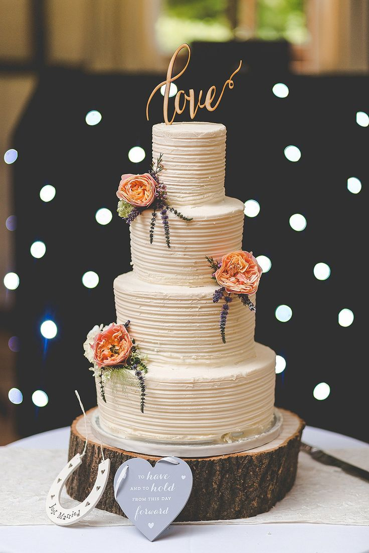 Four tier butter iced cake decorated with fresh flowers. Photography by Sam and Louise