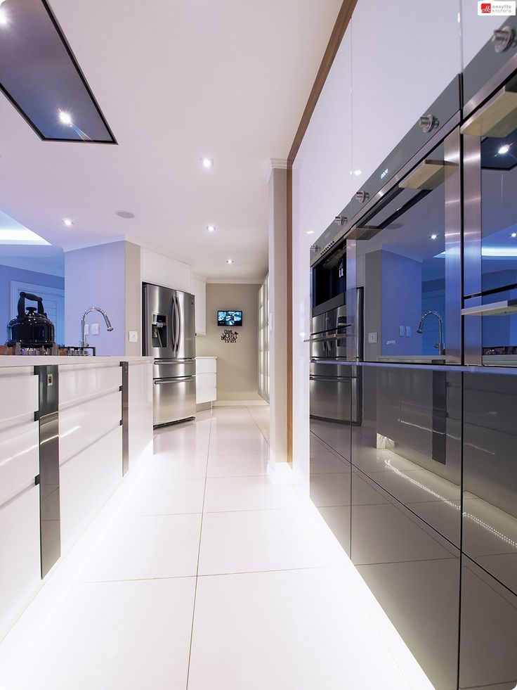 The end result is this streamlined, contemporary kitchen using a mixture of High Gloss White and American Walnut with glass and mirror finishes.  Built-in appliances create a luxurious look and feel. This is a kitchen they can enjoy for many years to come.