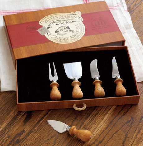 """Cheese Knife Set by Wildly Delicious. Cheese Knife Set is a 2011 sofi™ Award Silver Finalist for outstanding Non-Food Specialty Item. National Association for the Specialty Food Trade, Inc. Accompanied by a serving fork, the four knives are each proudly branded and feature Rosewood handles and high quality, Japanese stainless-steel blades shaped for a specific type of cheese. This five piece set contains knives that are 5"""" to 5 3/4"""" long. #961156 $29.99  www.lambertpaint.com"""
