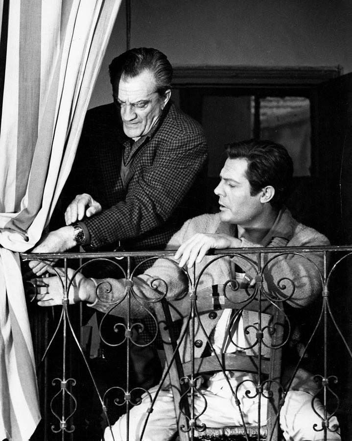 """Director Luchino Visconti with Marcello Mastroianni on the set of """"Lo Straniero"""" 1967"""