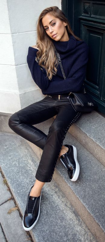Kenza Zouiten pairs a deep blue knit with studded leather trousers and black sneakers.   Shoes: Scorett, Trousers: Jofama.