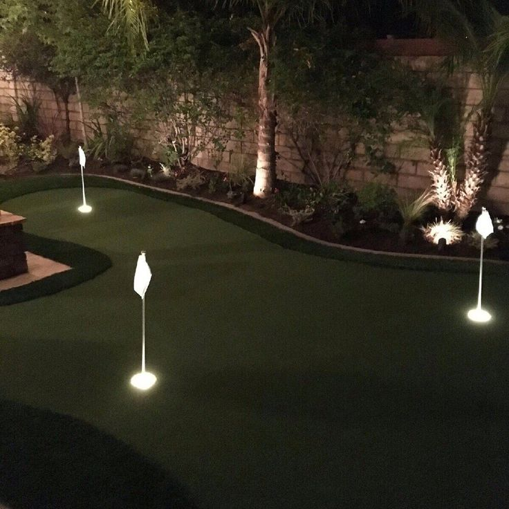 Backyard putting green with cup lights