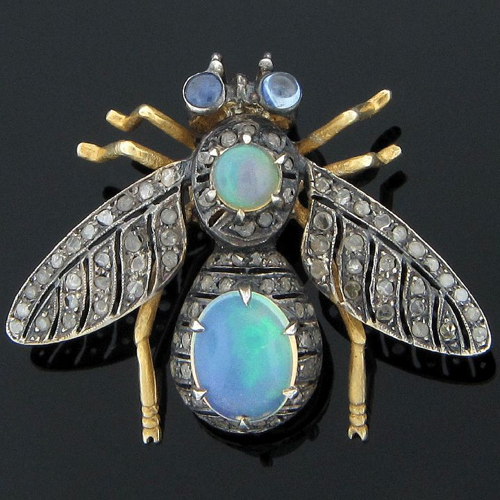Antique 9K gold jeweled bee pin, circa 1910. This bee pin is expertly hand made of 9 karat white and yellow gold. It has a prong set oval cabochon opal on the body at approximately 1.59 carats and a prong set round cabochon opal on the head at approximately .50 carat. Both opals are of fine quality. The bee has two bezel set round cabochon light blue sapphire eyes at approximately .18 carat total weight that are of good quality. Its wings and body are covered in 90 prong set cleaved and…