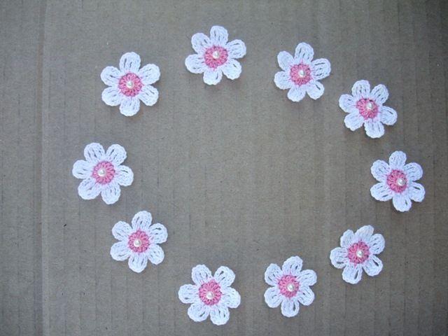 Flores em croché, feitas com linha nº12, com cerca de 3 cm de diâmetro e uma pérola ao meio. Ficam muito bonitas quando aplicadas em roupinhas de menina, fraldas, babetes e lençóis.