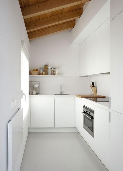 Petita cuina blanca amb línia minimal i tots els elements necessaris.