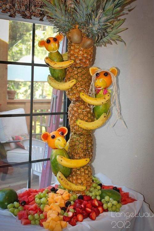 Monkeys made of fruit. climbing a pineapple tree
