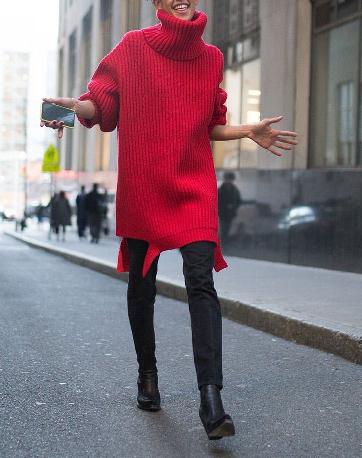 street style woman in skinny jeans and chunky sweater dress