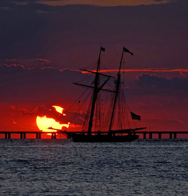 The Pride of Baltimore II on an evening sail, while participating in OpSail 2012, floats in front of the Chesapeake Bay Bridge Tunnel outside of Norfolk, Virginia. Photo by Brad Wikle