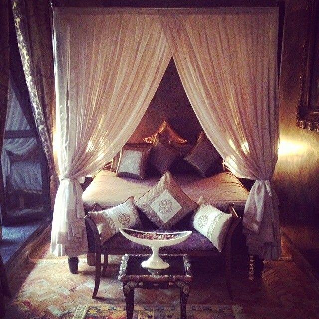"""A large four poster bed with gold and bronze cushions with cream curtaining draped at either side and a chaise lounge at the end on a gold patterned rug. """"Room for the weekend #marrakech #travel""""As snapped by Matthew Williamson on Instagram."""
