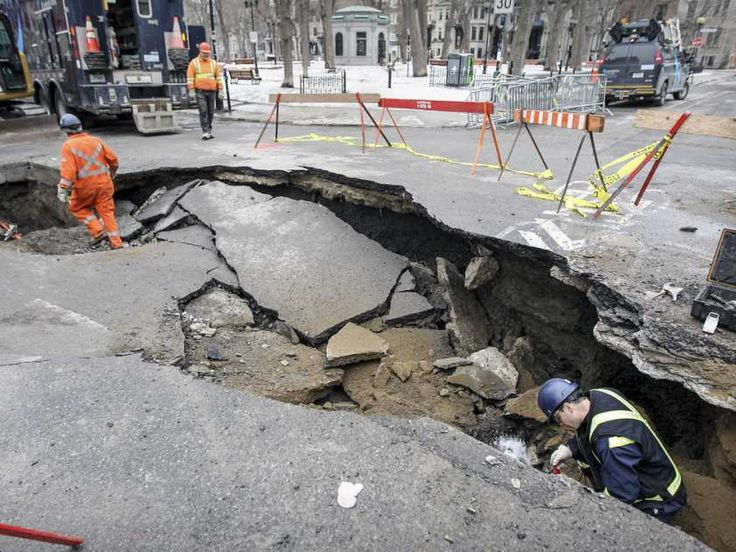 MONTREAL, QUE.: March 10, 2016 -- Workers walk in sinkhole that opened up at the corner of Laval St. and Square Saint-Louis in Montreal Thursday March 10, 2016.  The hole was caused by a water main break.  (John Mahoney / MONTREAL GAZETTE)