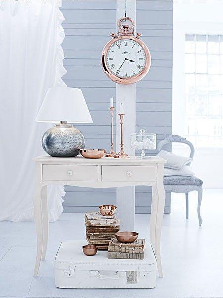 Die kupferfarbene Wanduhr passt sich aufgrund der Optik einer nostalgischen Taschenuhr besonders gut in ein pastelliges Wohnkonzept an.