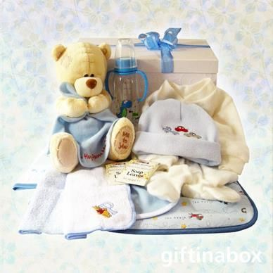 "Welcome to the new baby boy of the family. Give him lots of love with these beautiful products and his first ""me to you"" hug blanket teddy bear. All goods are lovingly presented in a large, white gift hamper box decorated with blue ribbons and tissue paper.   ""Me to You"" hug blanket teddy bear Hooded towel Full baby grow Baby beanie baby bib 2 x facecloths Baby bottle Baby waterproofs Sachet of bath soap leaves for mom"