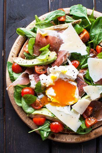 見目麗しいサラダは、材料が揃えば簡単に作れるサラダです。野菜はレタスなどでも代用できますが、なるべく生食用のほうれん草やルッコラを使って下さい。生ハムの塩気とチーズとよく合います。手に入らなければ、サニーレタスがオススメです。  材料) ベビーリーフ(ほうれん草)一掴み・チェリートマト4個(くし形に4つに切る)・パルマハム(生ハム)3-4枚・ハードチーズ(パルメジャーノチーズ等)スライサー等で削ったものを数枚・フレッシュミント数枚・黒胡椒・ポーチドエッグ(卵1個)・オリーブオイル・バルサミコ酢