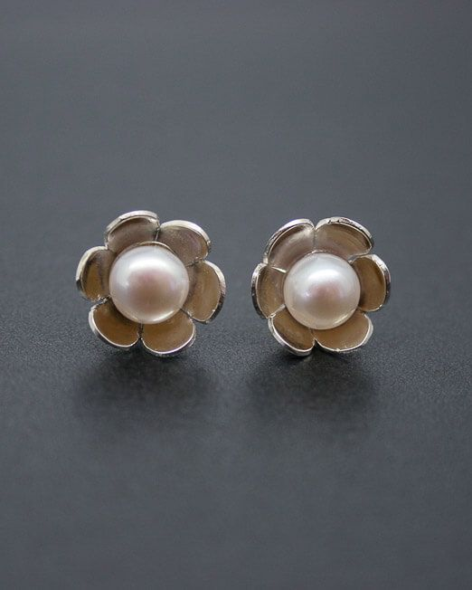 Silver daisy stud earrings with fresh water pearls.  Created by hand in our Porthleven studio.  The 12mm. daisies have been hand saw pierced from silver sheet, domed and set with a single 7mm. fresh water pearl.  Other pearl colours available are Pink, Black, Yellow and as listed; White.  We would be happy to create these earrings in mixed coloured gold.  Please get in touch for an estimate.  #Bridal #Daisy #Earrings #Floral #Pearl #Silver #Starboard #Wedding