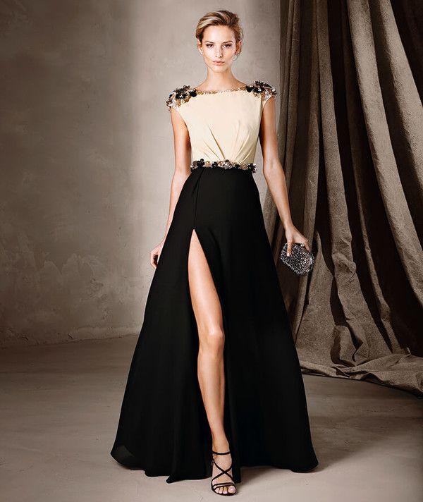 Vestido largo bicolor con una sugerente apertura frontal en la falda y detalles de pedrería en los hombros y el cinturón.