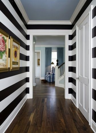 Horizontal stripes make a hallway feel longer. Gold accents add style and a painted ceiling highlight the black and white stripes.
