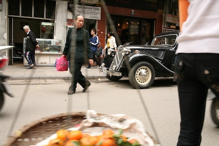Vintage car in the busy streets of Hanoi old town, Vietnam