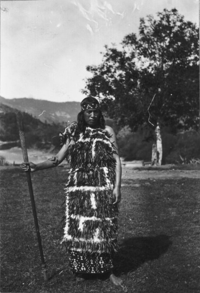 Photograph of Ada Pokiha modeling a fine feather cloak with a taniko border, at Koroniti