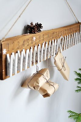 "DIY Little Gift Rack made from a simple piece of 1 x 4 or 6 inch wood and clothes pins painted white. Would lbe perfect for the ""12 Days of Christmas"" or Advent"