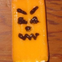 My kids love creamsicles – the ice cream on a stick covered with orange flavored ice. We had some creamsicles and some black icing gel so we decided to have some Halloween fun with them. We made these Jack O Lantern creamsicles.    This would be a fun snack/craft for a den meeting. You have to work fairly quickly so they don't melt though, so I wouldn't recommend it for a big group.: Kids Stuff, Jack O' Lantern