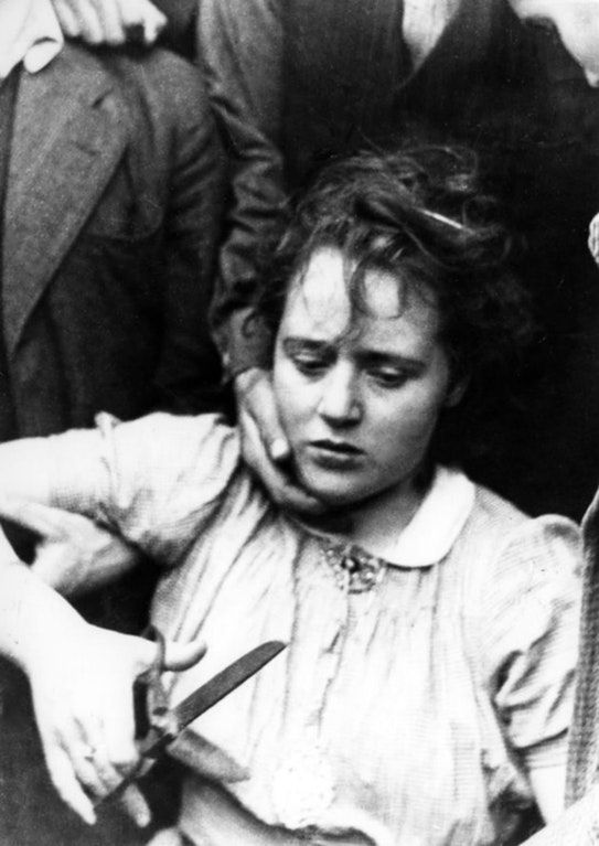 A Dutch woman accused of having a romantic relationship with a German soldier is held by members of the Dutch Resistance and is punished by having her head shaved following the liberation of the province of Overijssel. April, 1945.