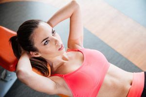 Attractive concentrated young woman athlete doing exercises lying on bench in gym