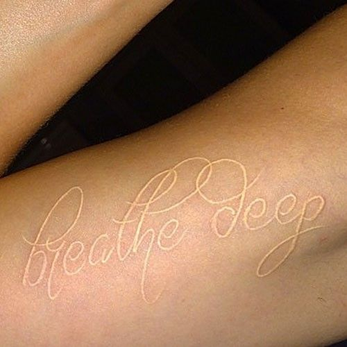 """Cara Delevingne's 20 Tattoos & Meanings   Steal Her Style - Cara Delevingne has the words """"breathe deep"""" tattooed in white ink on the inside of her upper right arm. It was done by artist Bang Bang in July 2014."""