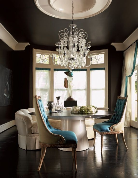 It is difficult to imagine this dining room without the dark chocolate ceiling to mimic the walls and flooring.  These dark elements are contrasted by the off-white base/crown molding that ties into the cream colored furniture.  The blue inner chair upholstery and drapery trim adds just a touch of elegance and flair in perfect proportion.  This is one dining room certain to make your mouth water!
