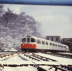 Piccadilly line 1973 tube stock train in a winter landscape. View taken at Oakwood sidings. Unknown photographer, 1973