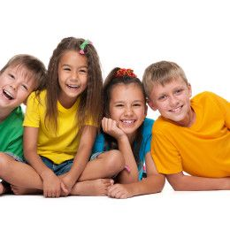 Four laughing children are lying on the white background