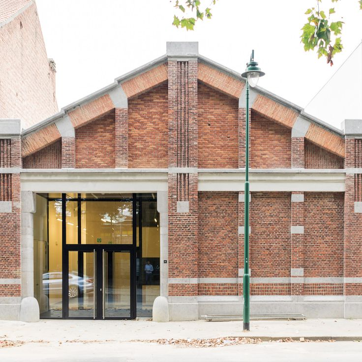 This red brick building that once formed part of a cigarette factory in Brussels has been converted into a council office with minimalist interiors.