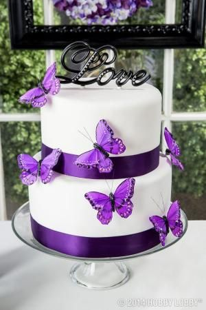This white-and-purple wedding cake is topped off with a little love! by imogene
