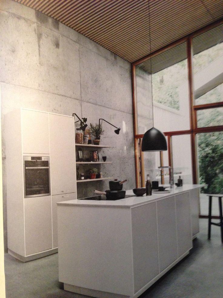 Witte keuken, grijze betonvloer en op achtergrond houten raamspijlen