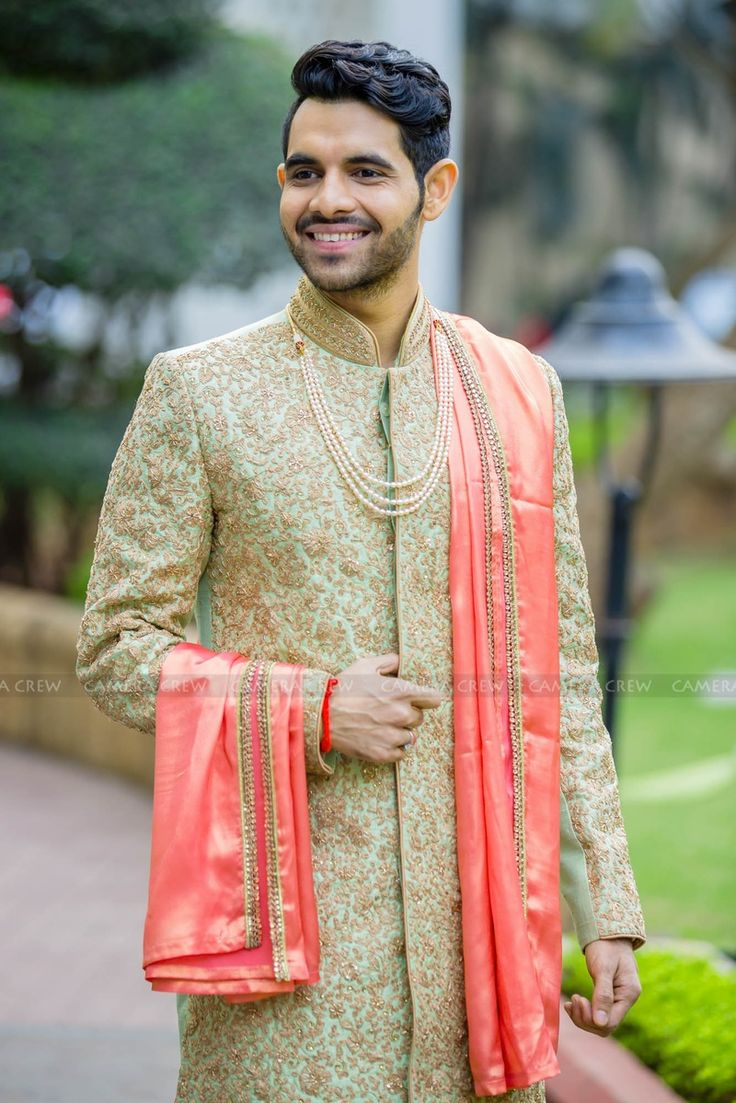 Pastel green sherwani embellished with resham gold embroidery and orange kinnari dupatta. This groom sure know how to turn heads.