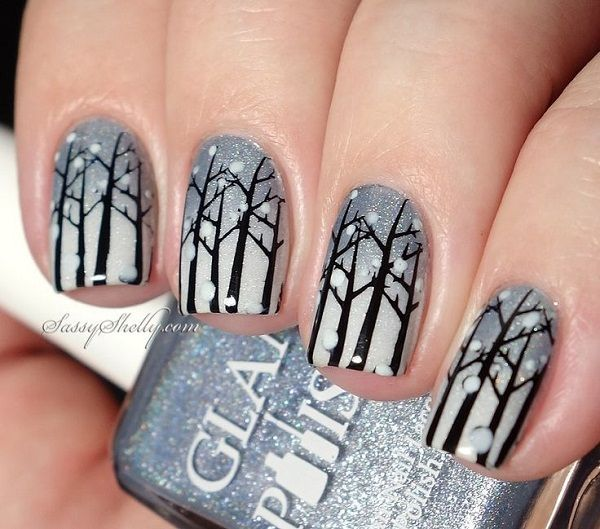 Wonderful looking winter nail art design. The design shows silhouettes of trees amidst snow falling gently from the sky. Glitter polish is also used to top off the layers.