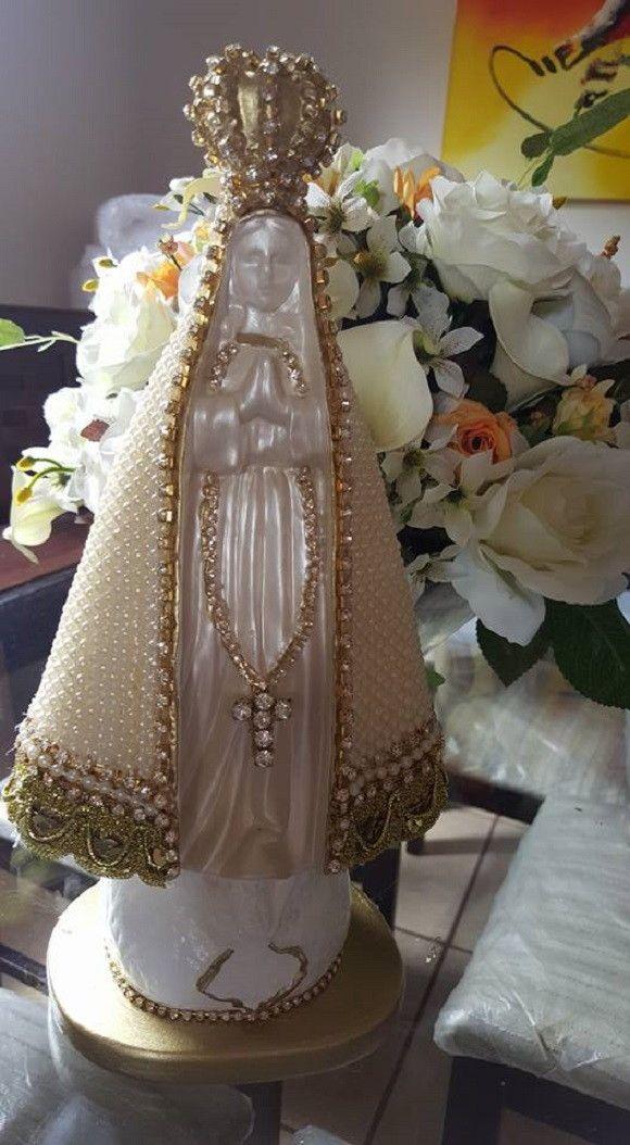 Nossa Senhora Aparecida, em gesso, perolada e com manto revestido manualmente com pérolas e detalhes em strass, com 30 cm de altura.