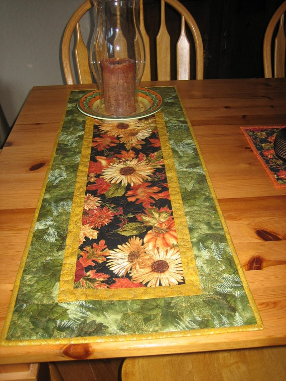 Karen of Tahoe Quilts says: Sunflowers are so vibrant, and this print shows them off beautifully! This table runner features large sunflowers against a black background in the center of the runner. There are also large leaves and partial pumpkin and fruit images. A gold fabric was used for both the small inner border and outside binding strip. To pick up the green colors, a fabric with gold outlined leaves was used for the outside border.