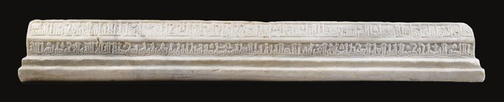 An important Fatimid carved marble cenotaph, Egypt or Tunisia,  dated 402 AH/ 1011 AD of typical form, with step base and polygonal upper section, decorated along the sides with long friezes of carved foliated Kufic script, the ends with stylised palmettes  160cm. length 22cm. height 17cm. width inscriptions  The basmala, the tasliya; Qur'an chapters CXII (al-Ikhlas); IX (al-Tawba), verses 128 & 129 and II (al-Baqara), verse 255, followed by:  'This is the tomb of al-Qamar daughter of…