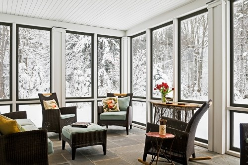 This sun porch has windows in the winter, but swaps out to screens in the summer (by Whitten Architects)