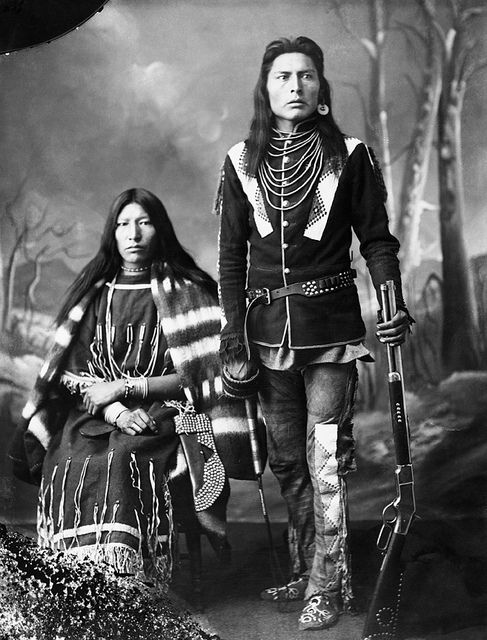 First Nations man and his wife. 1886. Photographer, Alexander J. Ross, Calgary, Alberta. - Studio portrait. Man holding gun with studding on stock, and whip.