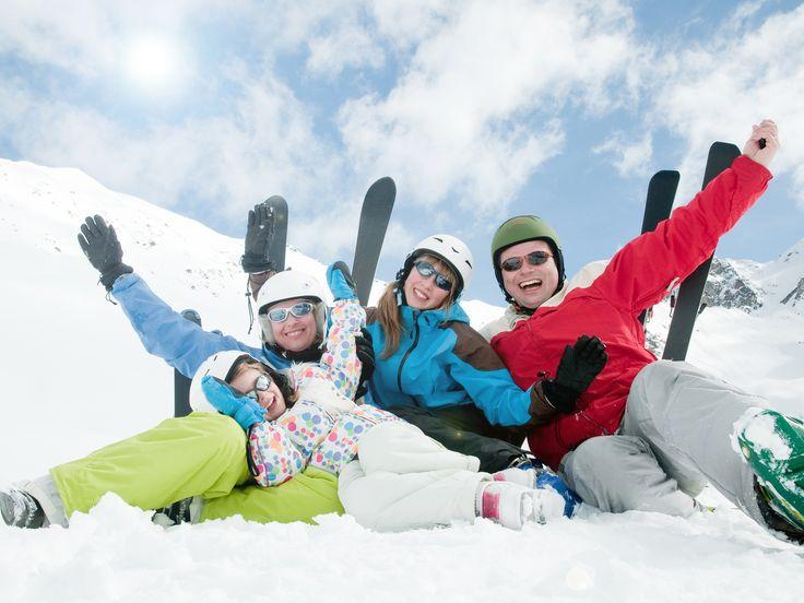 Winter, ski, sun and fun - happy skiers in ski resort