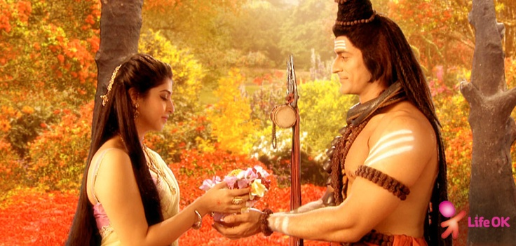 Mahadev lovingly presents a flower garland to Parvai